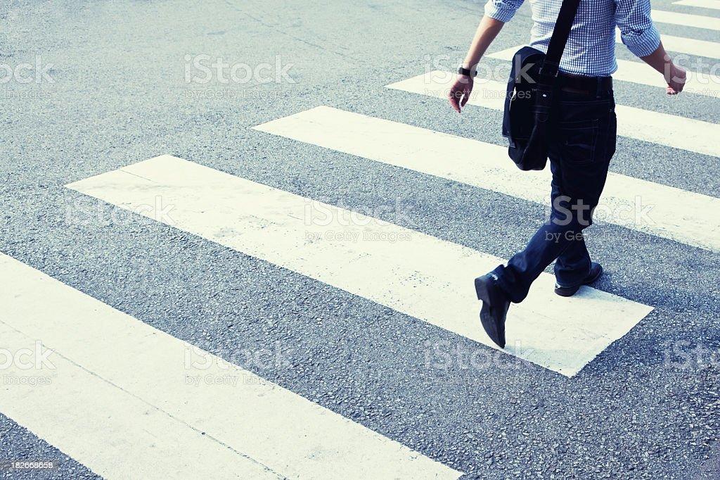 Man rushing across zebra crossing stock photo