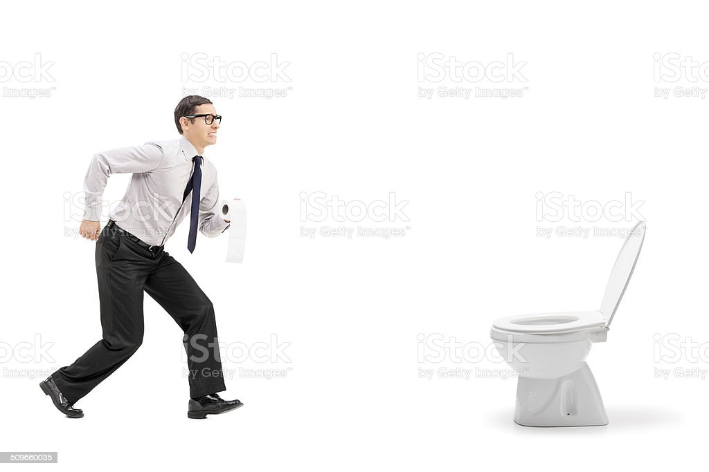 Man rushing to a urinal and holding toilet paper stock photo