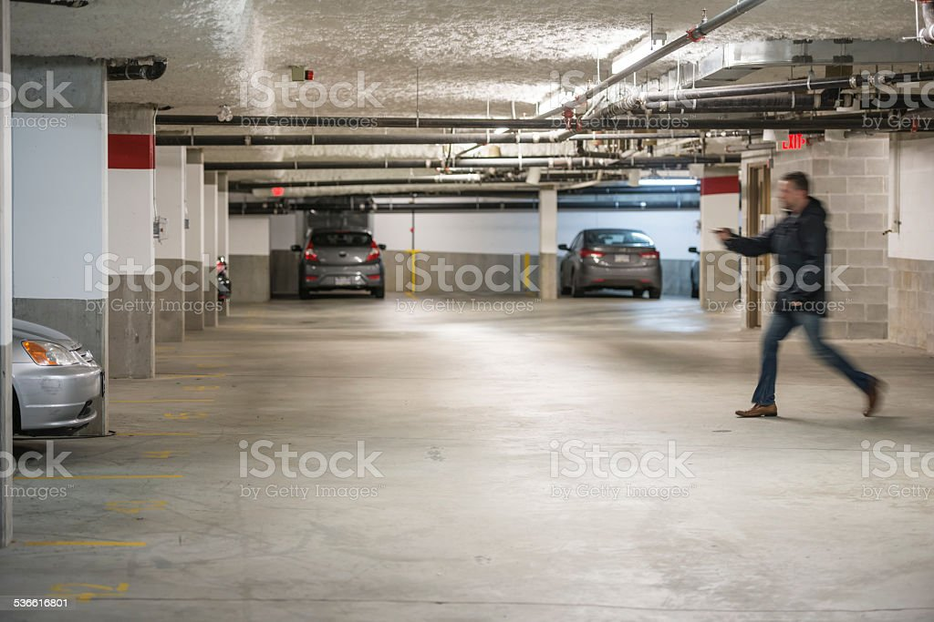 Man Rushing To Car In Parking Garage stock photo