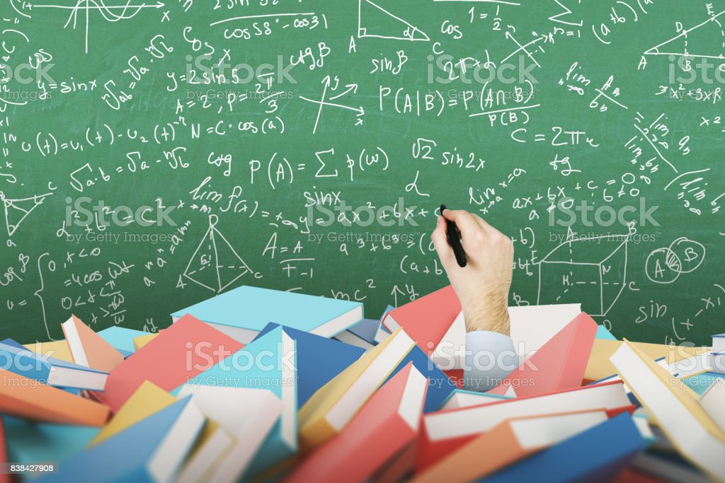 Man s hand with a marker, pile of books, formulas stock photo
