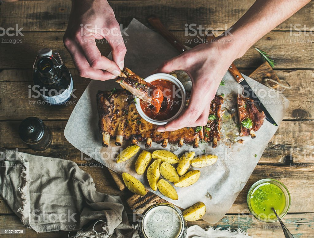 Man' s hands dipping piece of roasted pork to ketchup stock photo