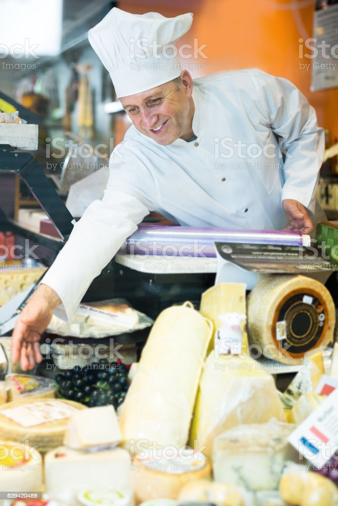 Man salesman selling soft and hard cheese in store stock photo