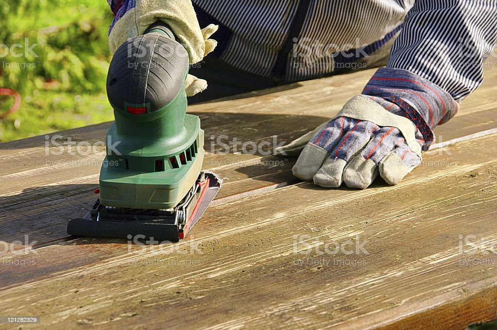 A man sanding down a wood panel stock photo