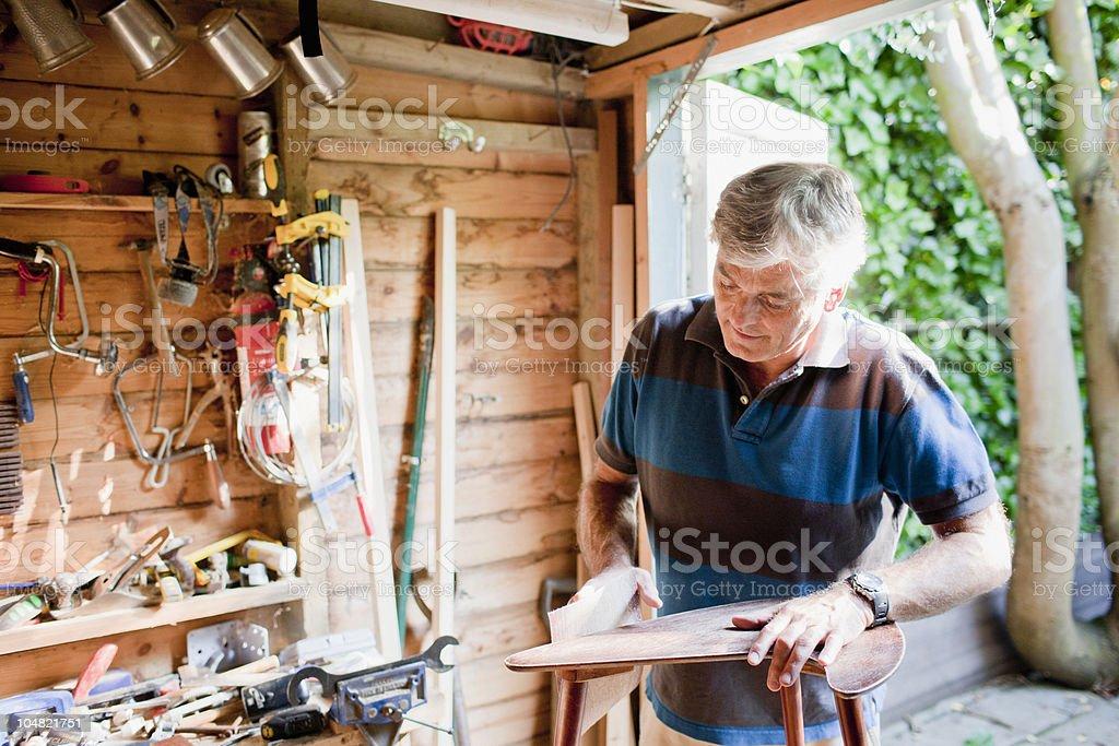 Man sanding wood in workshop stock photo