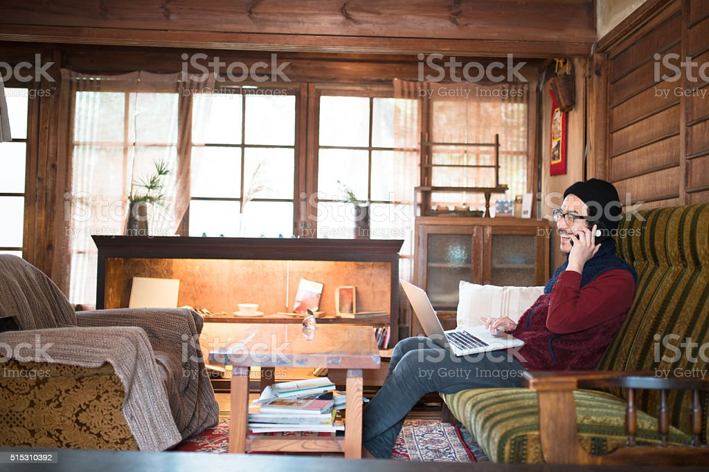 Man sat in a cafe using his computer stock photo