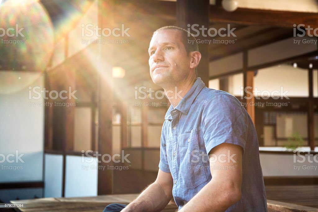 Man sat looking thoughtful at a Japanese Temple stock photo