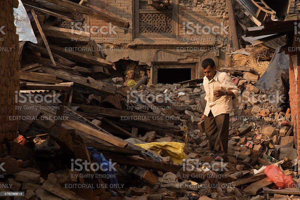 Man saves what he can after earthquake in Nepal. stock photo