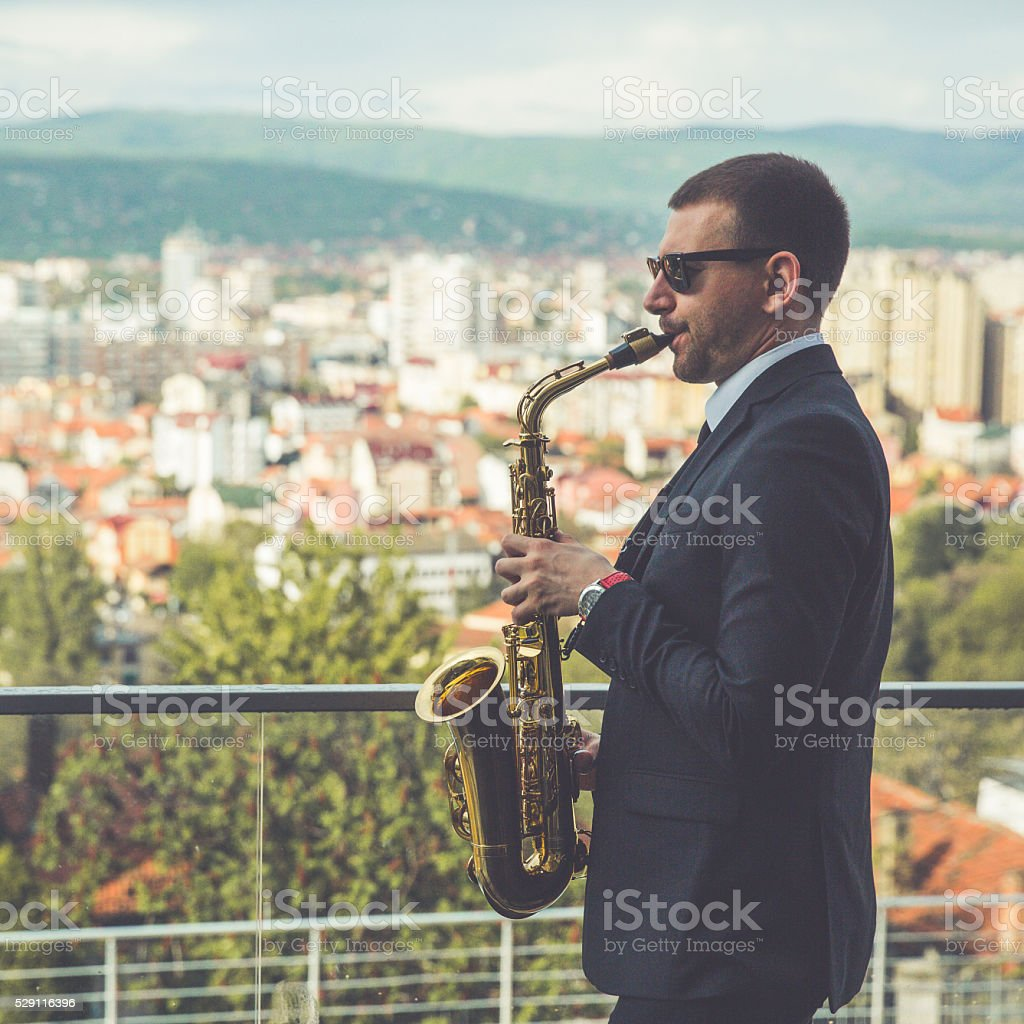 Man saxophonist playing saxophone stock photo