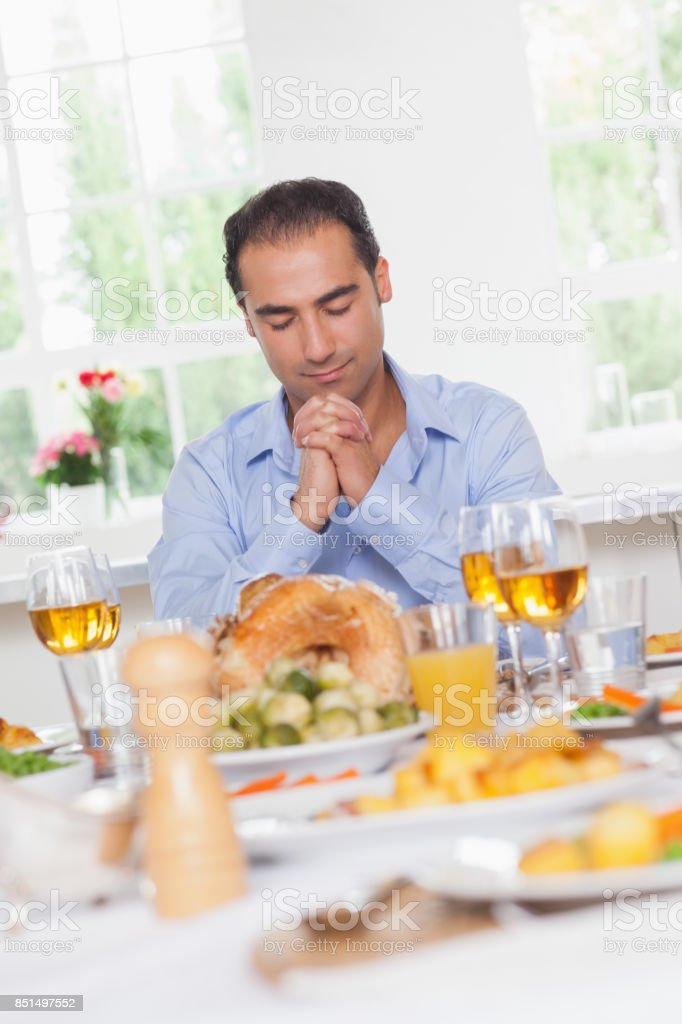 Man saying grace before dinner stock photo