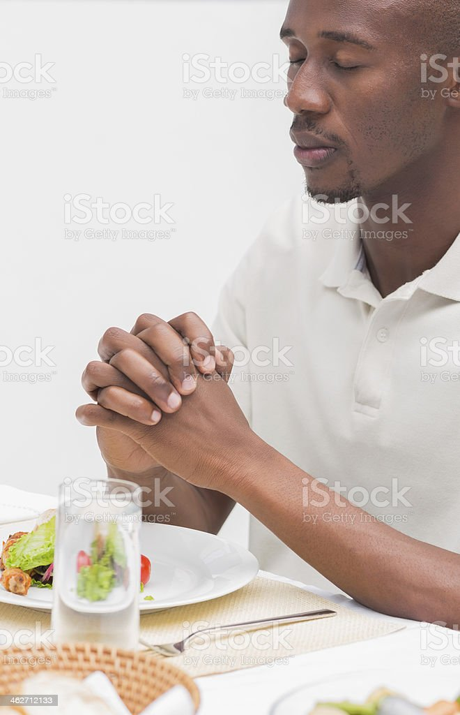 Man saying grace before having dinner stock photo