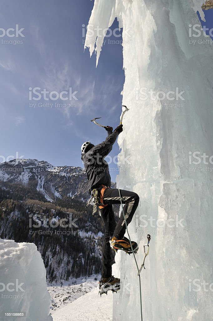 A man scaling a vertical ice cliff  stock photo