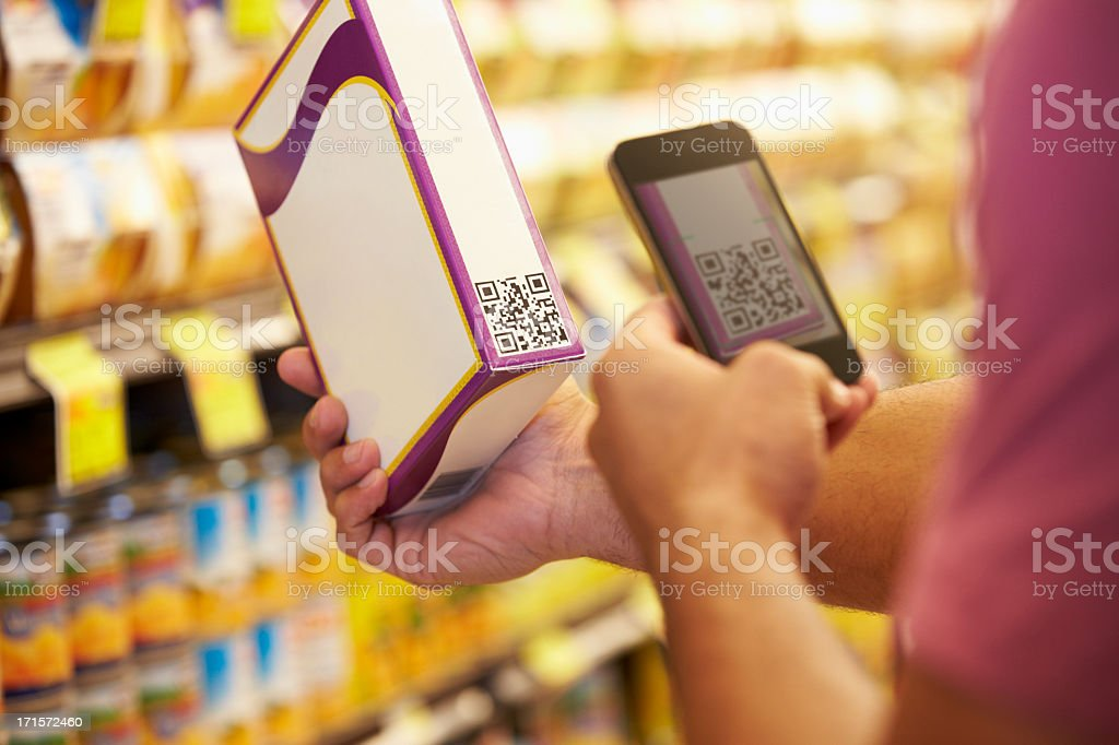 Man Scanning Voucher Code In Supermarket With Mobile Phone -NOTE