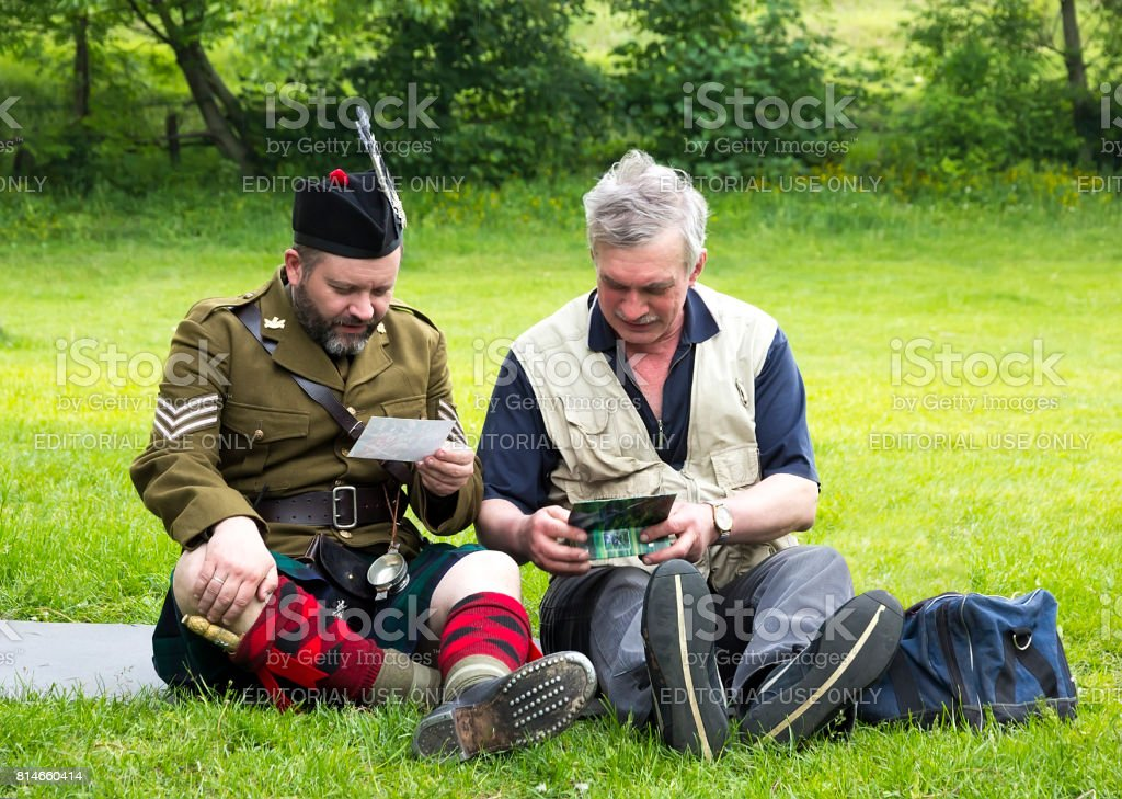 A man Scottish and an elderly man looking at album stock photo