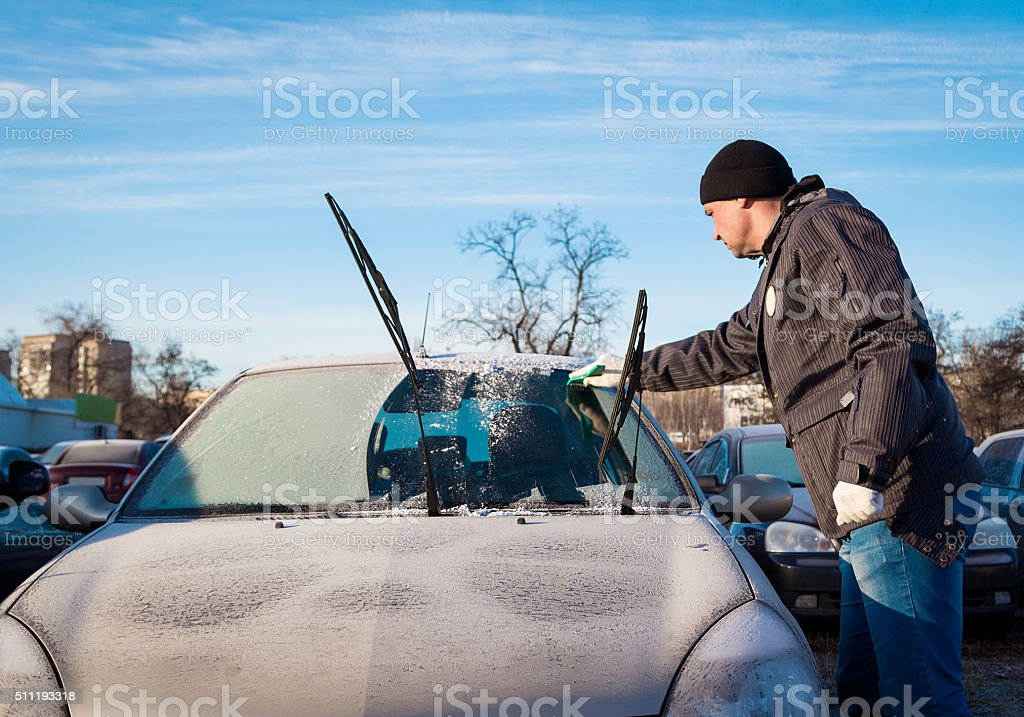 Man scraping front windshield stock photo