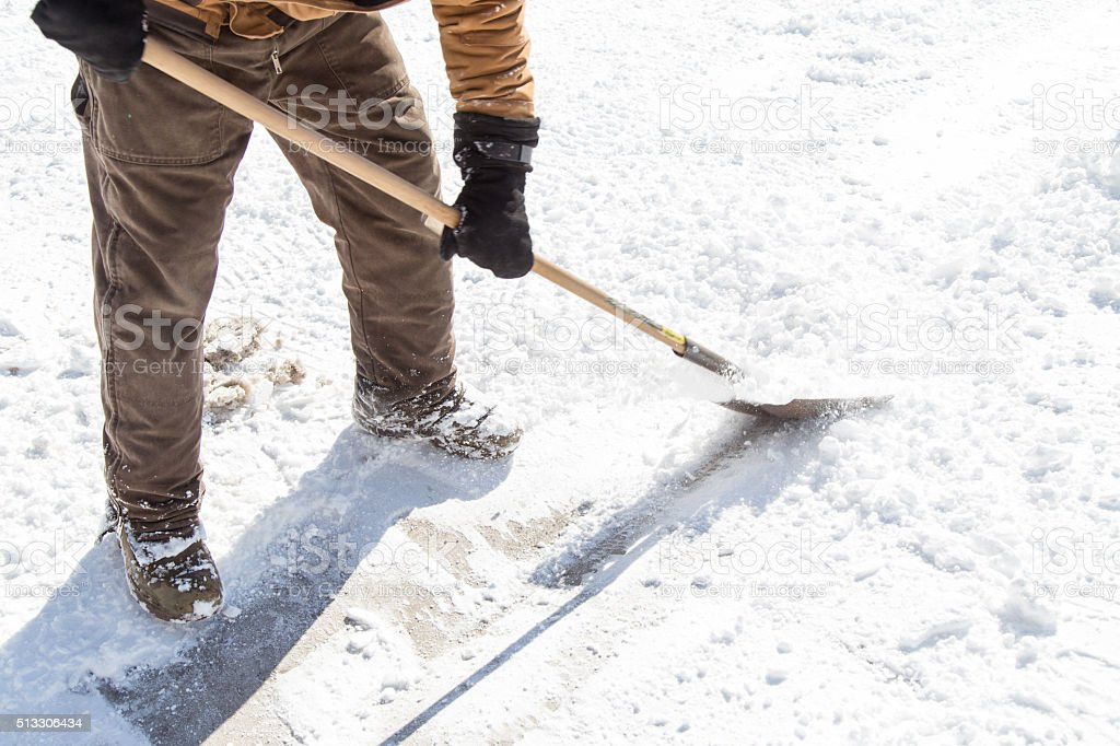 man scraping ice with shovel stock photo