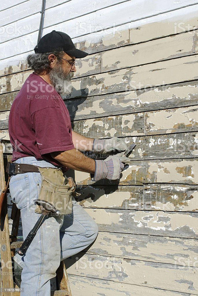 Man Scraping Paint from House stock photo