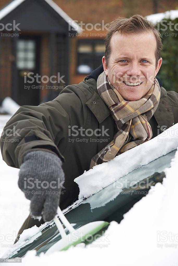 Man Scraping Snow From Car Windscreen stock photo