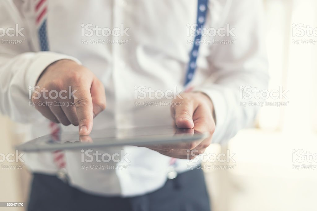 Man scrolling images, reading news on tablet PC, hands closeup stock photo