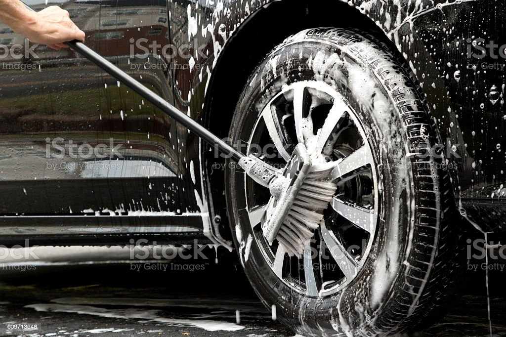 Man scrubbing soapy car tire and wheel with brush stock photo
