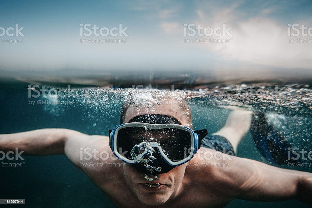 Man scuba diving underwater in sea with mask stock photo