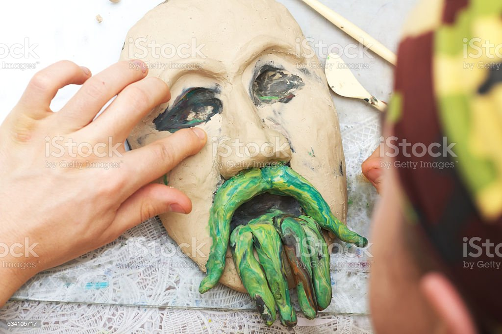 Man sculpting plasticine form of face stock photo
