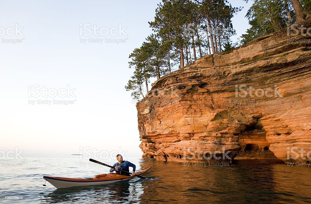 Man Sea Kayaking in The Apostle Islands National Lakeshore. stock photo