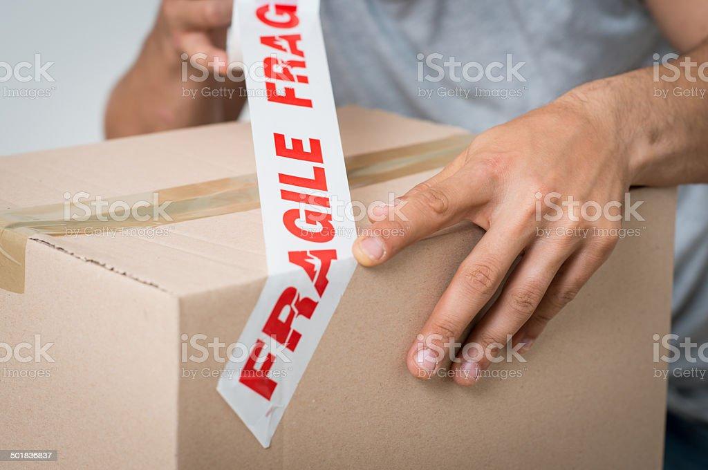 Man Sealing Box With Fragile Adhesive stock photo