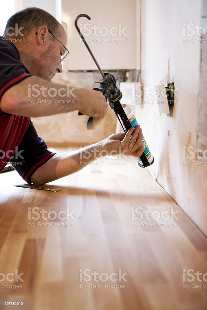 Man sealing the kitchen counter with caulk gun. stock photo