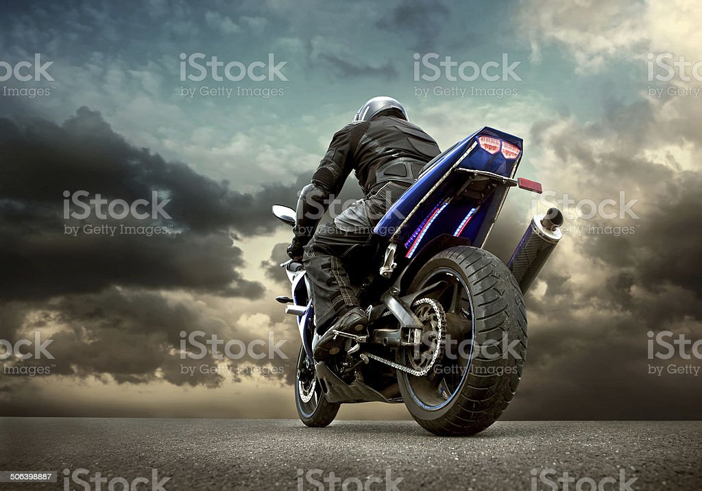 Man seat on the motorcycle under sky with clouds royalty-free stock photo