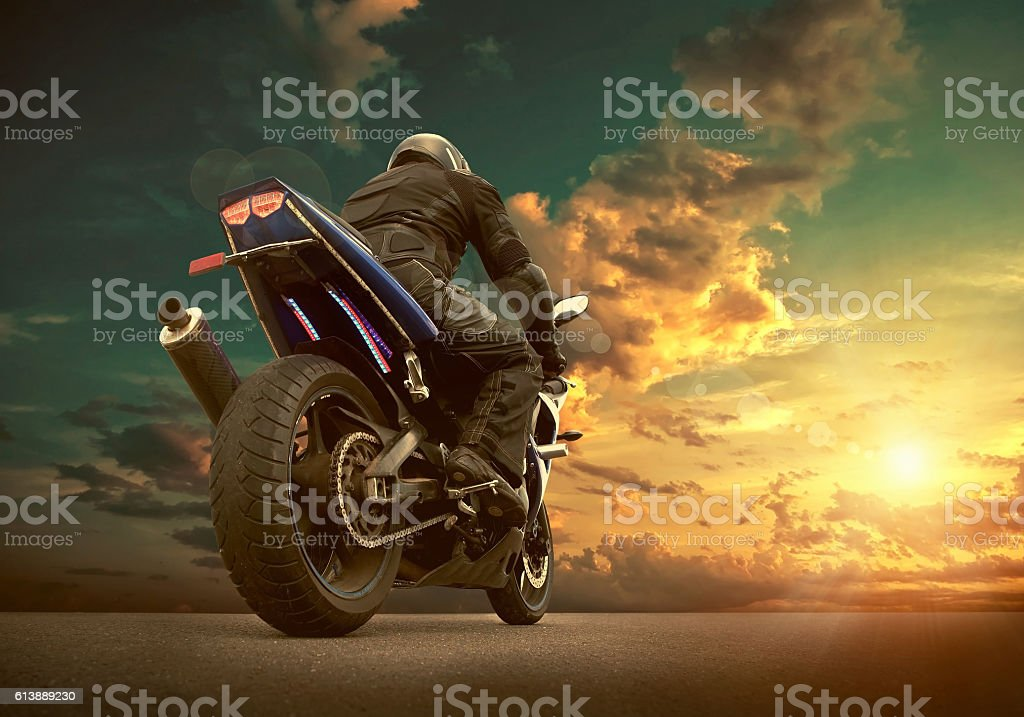 Man seat on the motorcycle under sky with clouds stock photo