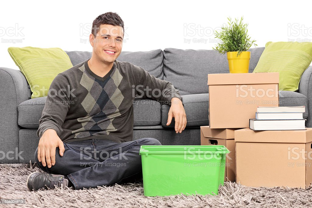Man seated on the floor by a bunch of boxes isolated on white...