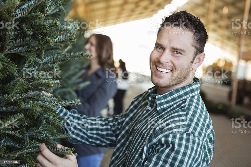 Man selecting Chrismas tree to purchase at outdoor farm royalty-free stock photo
