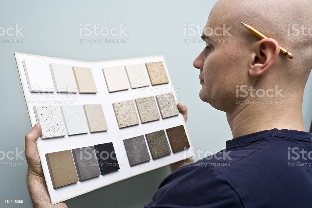 A man selecting counter top design from a samples in a book royalty-free stock photo