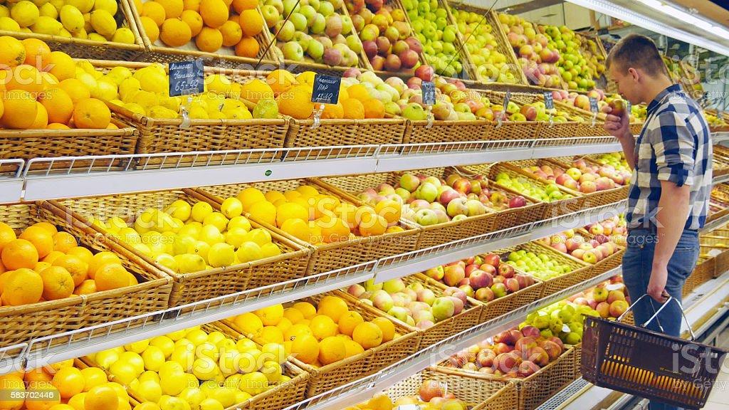 Man selecting fresh red apples in grocery store produce department foto de stock libre de derechos