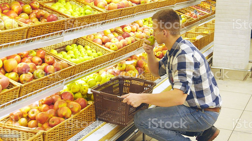 Man selecting fresh red apples in grocery store produce department foto de stock libre de derechos