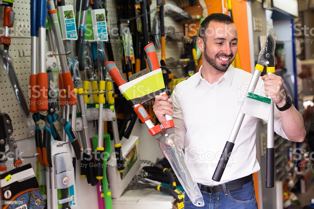 Man selecting household tools in store stock photo
