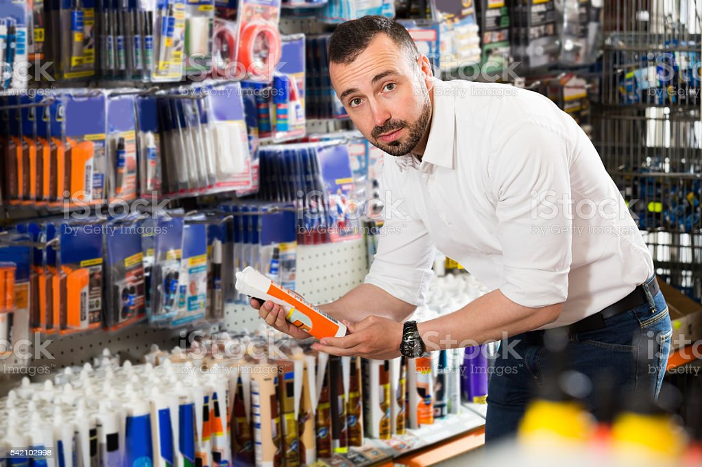 Man selecting sealant in household store stock photo