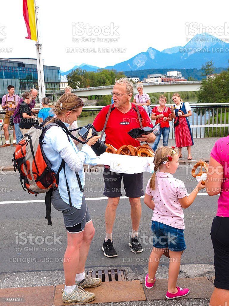 Man seling baked pretzels  on Villacher Kirchtag costume paradein, Austria stock photo
