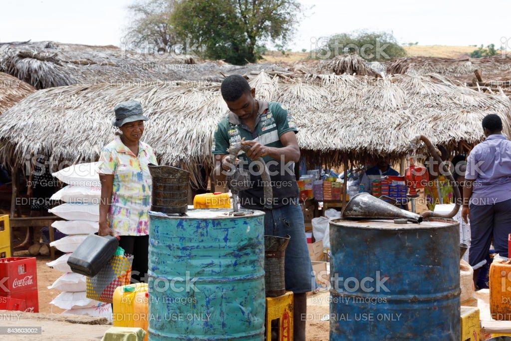 Man sell petrol on rural Madagascar marketplace stock photo