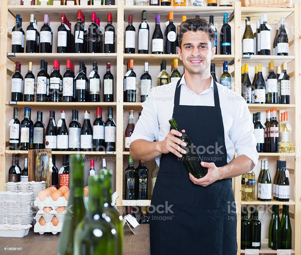 man seller holding bottle of wine in shop stock photo