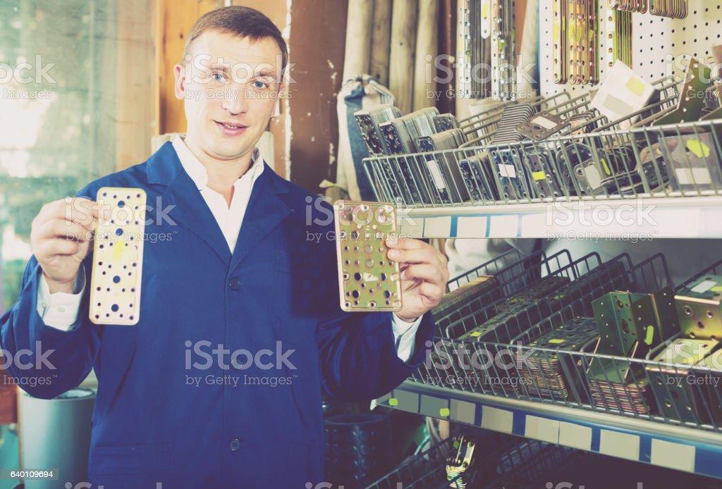 man seller wearing uniform having metal furniture in hands stock photo