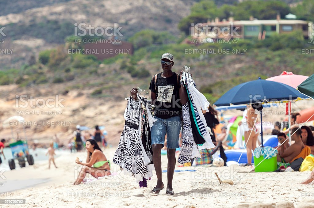 Man selling clothes in the beach stock photo