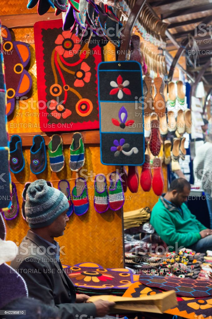 Man selling handicraft slippers and carpets stock photo