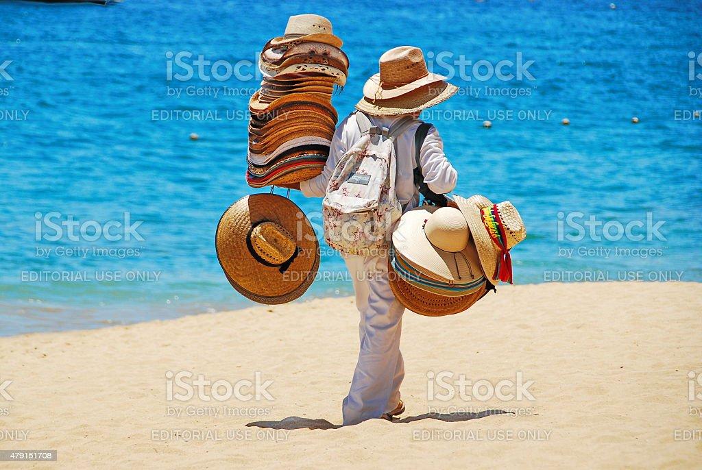 Man Selling Hats on Beach stock photo