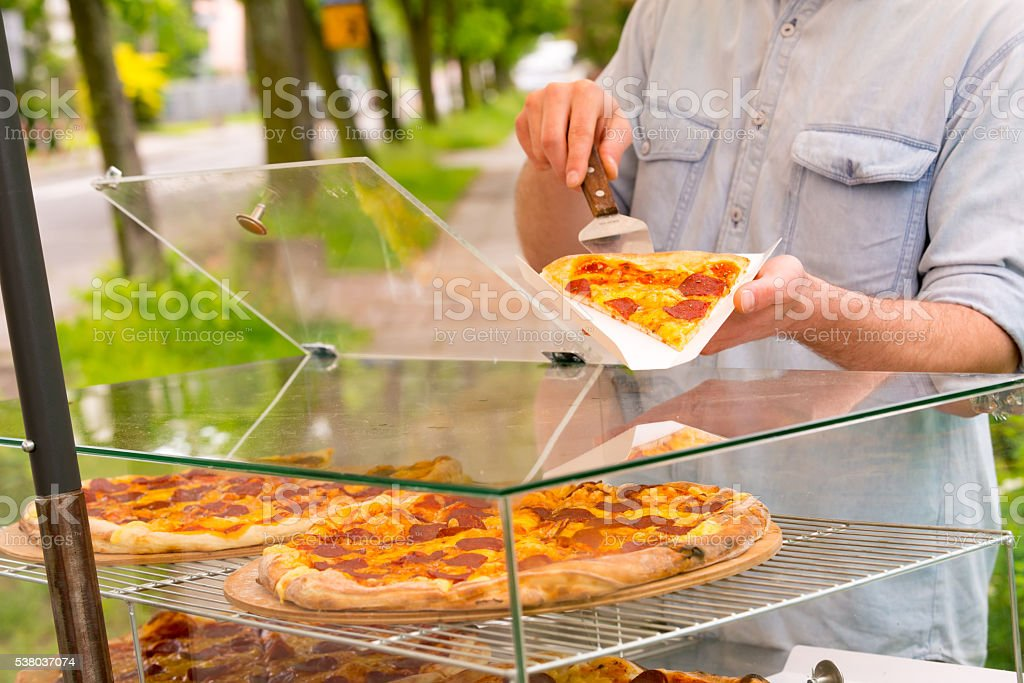 Man selling pizza by slice stock photo