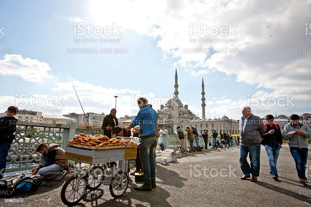 Man selling pretzels to fishermen on Galata Bridge, Istanbul stock photo