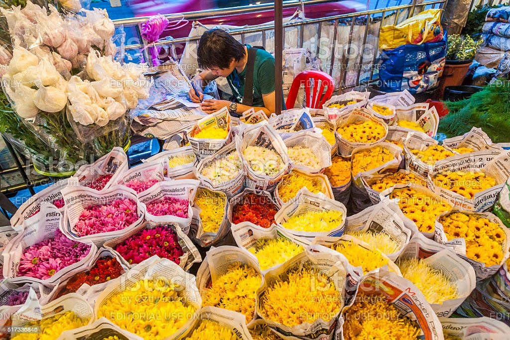 man sells colorful flowers at the flowermarket in Bangkok early stock photo