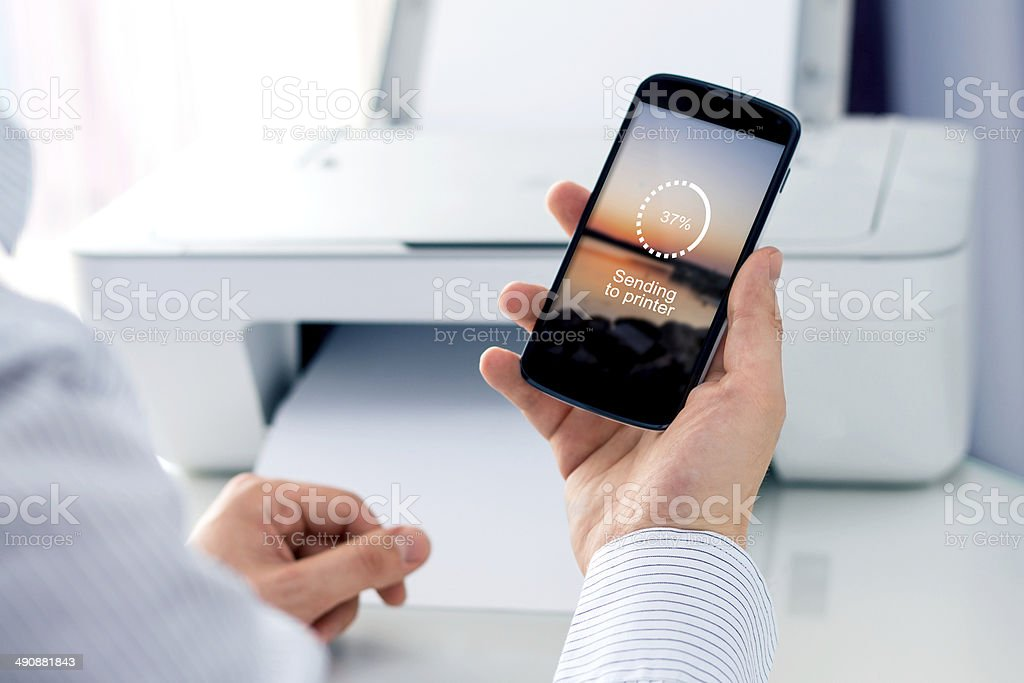 Man sending a photo to wireless printer stock photo