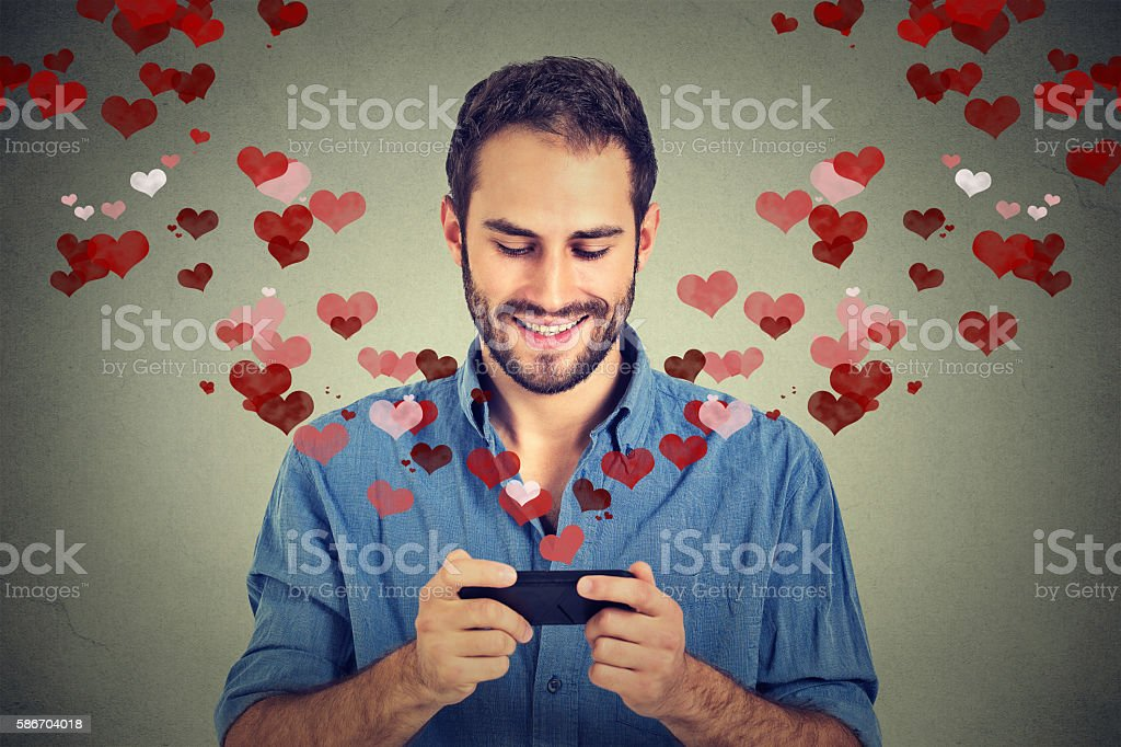 man sending love sms message on mobile phone stock photo