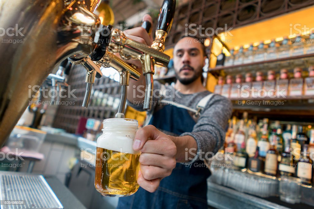 Man serving beer at a pub stock photo